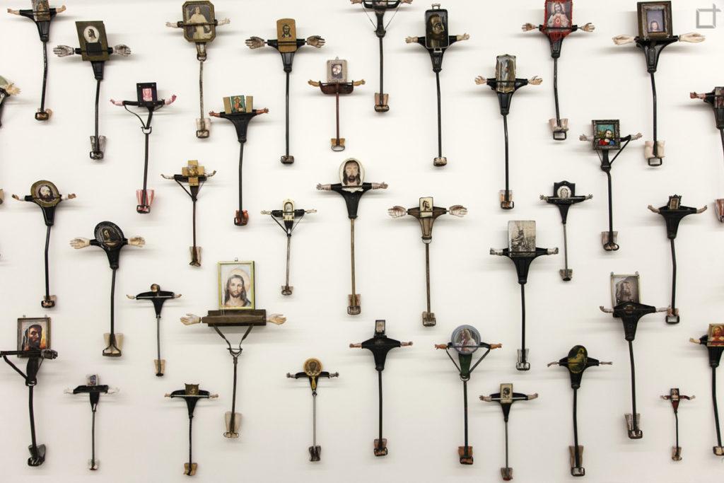 Tanti Crocifissi appesi al muro - Installazione Artistica Fondazione Prada - insulto alla cristianita