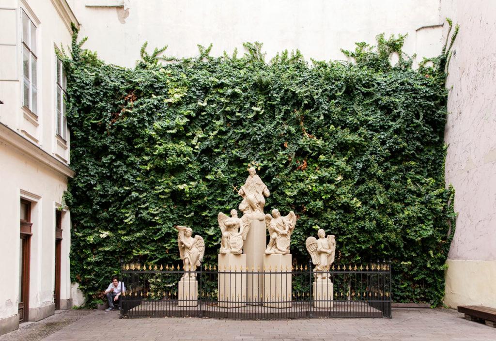 Cortile e Statue davanti a Facciata verde del Palazzo Primaziale