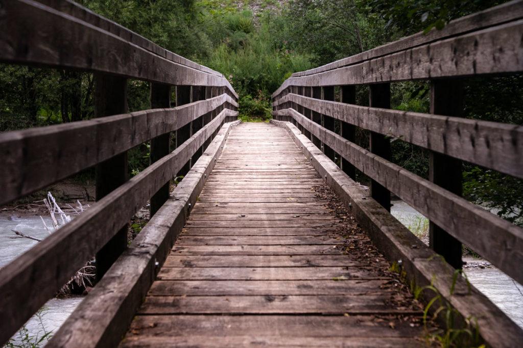Attraversare il ponte di legno sul fiume - Biciclettata magica in Trentino Alto Adige