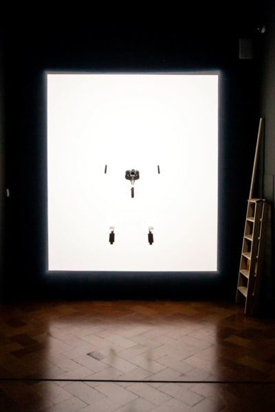 Luminosity - Donna sospesa su di un sellino abbagliata dalla luce - Performance di The Cleaner a Palazzo strozzi di Firenze