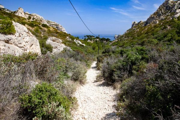Sentiero dritto fino acqua turchese nei calanchi di Sugiton