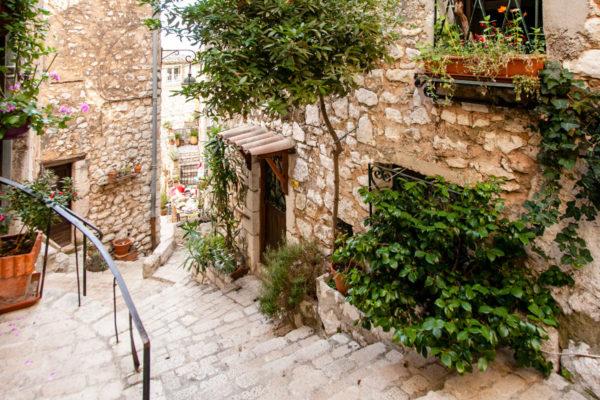 Vegetazione e scalinate tra le case di pietra del borgo provenzale di Tourrettes sur Loup
