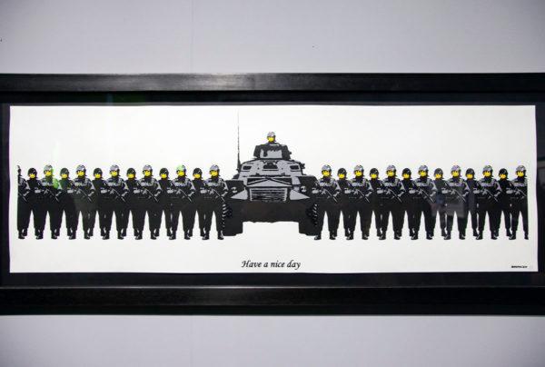 Have a nice day - soldati con carrarmato e smile al posto del visto - Opera di Banksy