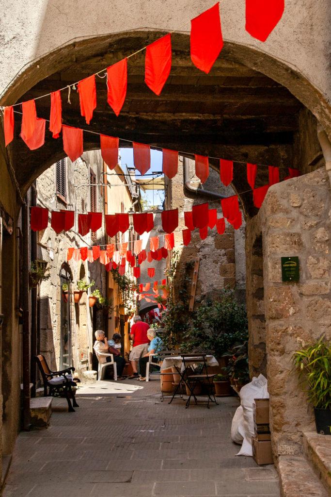 Bandierine rosse tra gli archi del borgo di Pitigliano - Cosa vedere in Maremma