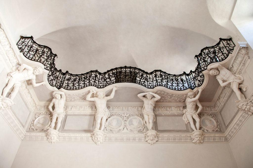 Balconcino per musicisti con balaustra in ferro battuto e telamoni a sostegno