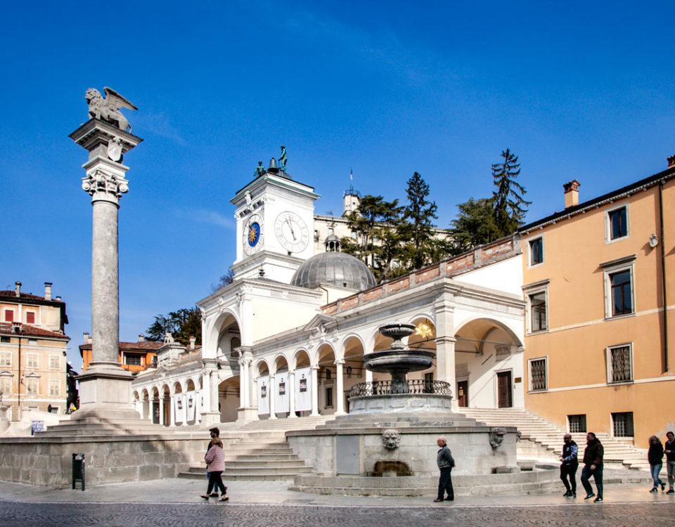Piazza della Libertà con Fontana e colonna con leone di Venezia - Porticato di San Giovanni e Torre dell Orologio