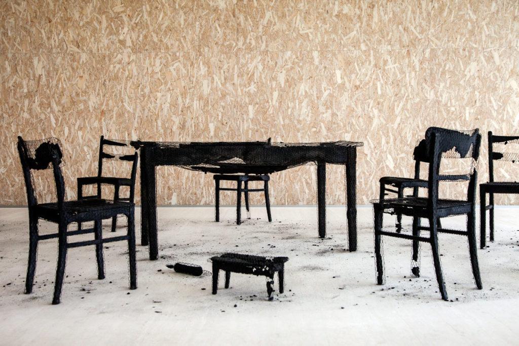 Tavolo e sedie bruciate in rete metallica - Remains of the Day di Mona Hatoum - Torre di Fondazione Prada