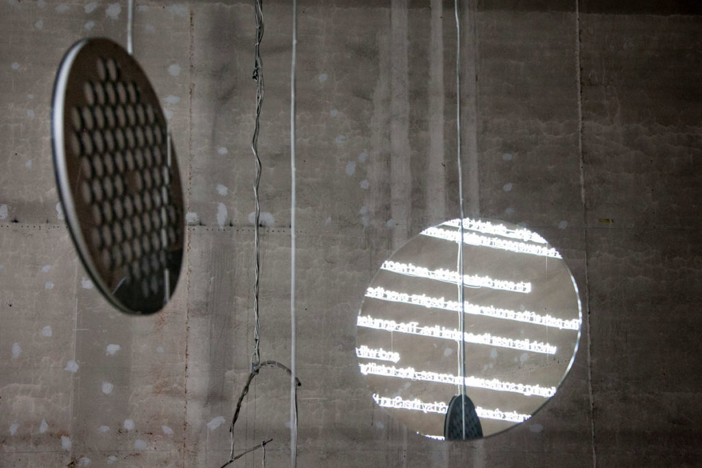 Opera E=C=L=I=P=S=E riflessa nei pannelli di C=O=N=S=T=E=L=L=A=T=I=O=N - Le sculture luminose e sonore di Cerith Wyn Evans ad Hangar Bicocca