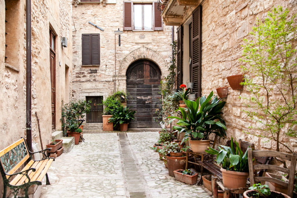 Vasi e fiori tra gli edifici in pietra del borgo
