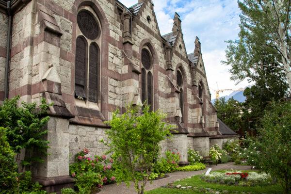 Fiancata della chiesa evangelica di Merano con aiuole fiorite